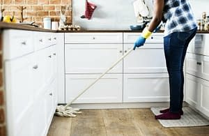 Picture of woman with gloves on mopping the kitchen floor